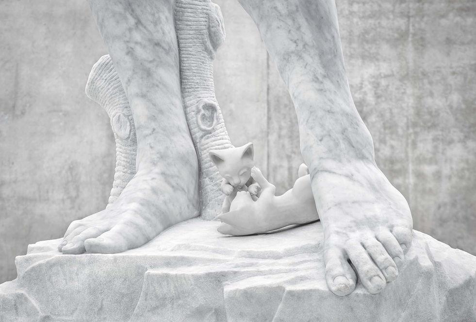 """Les jambes du """"David"""" de Michel-Ange, reproduites à l'échelle 1:1 en marbre de Carrare, avec des chatons imprimés en 3D sur une plateforme en résine blanche, et sol."""