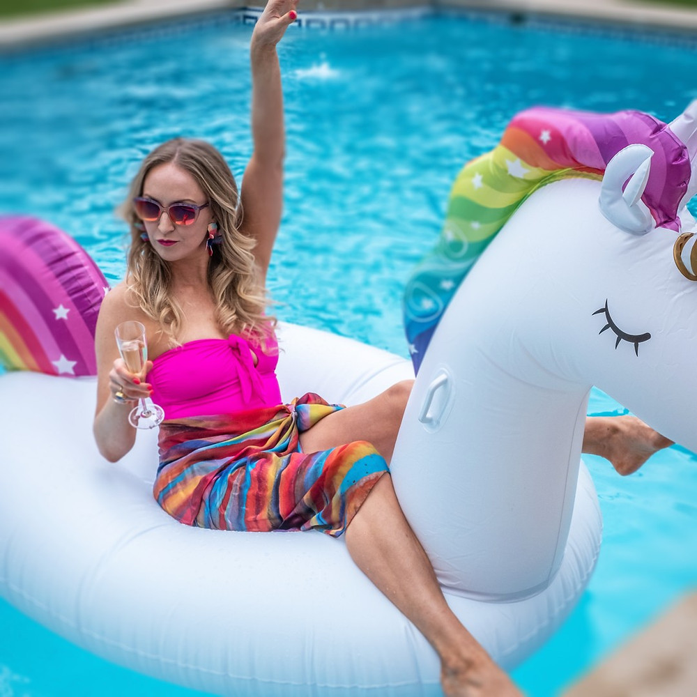 Alana Kay in a swimming pool on an inflatable unicorn