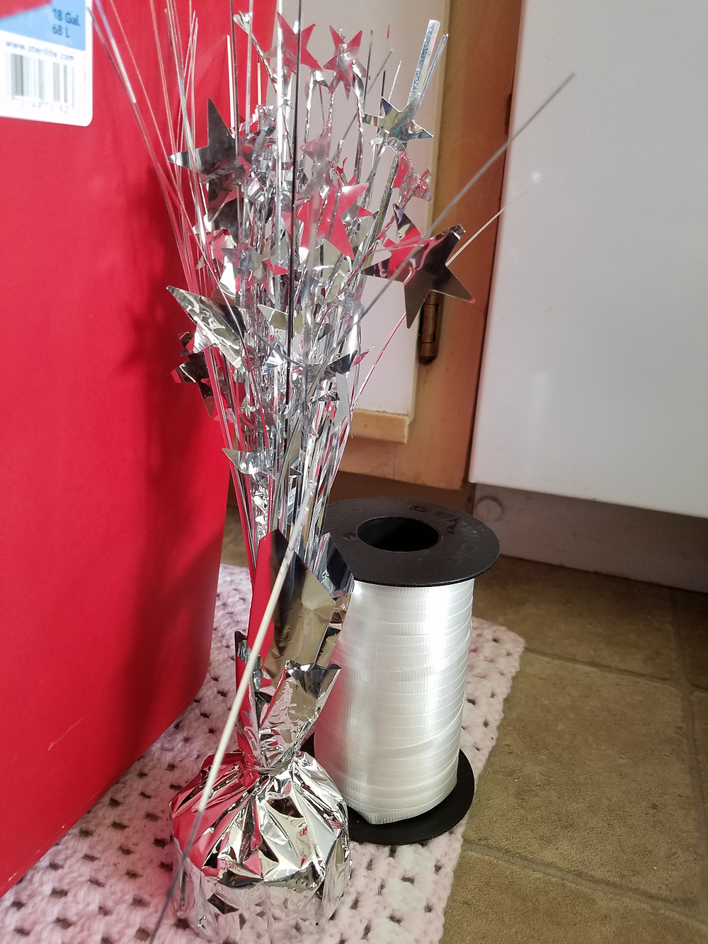 A silver balloon weight- metallic streamers and stars come out of it. A roll of white ribbon.