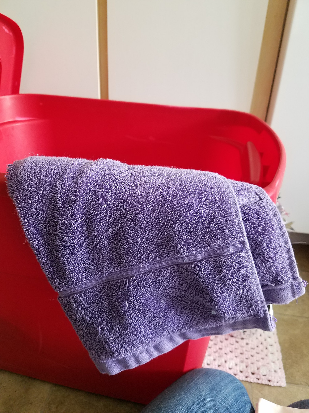 A purple hand towel draped over the side of the red bin.