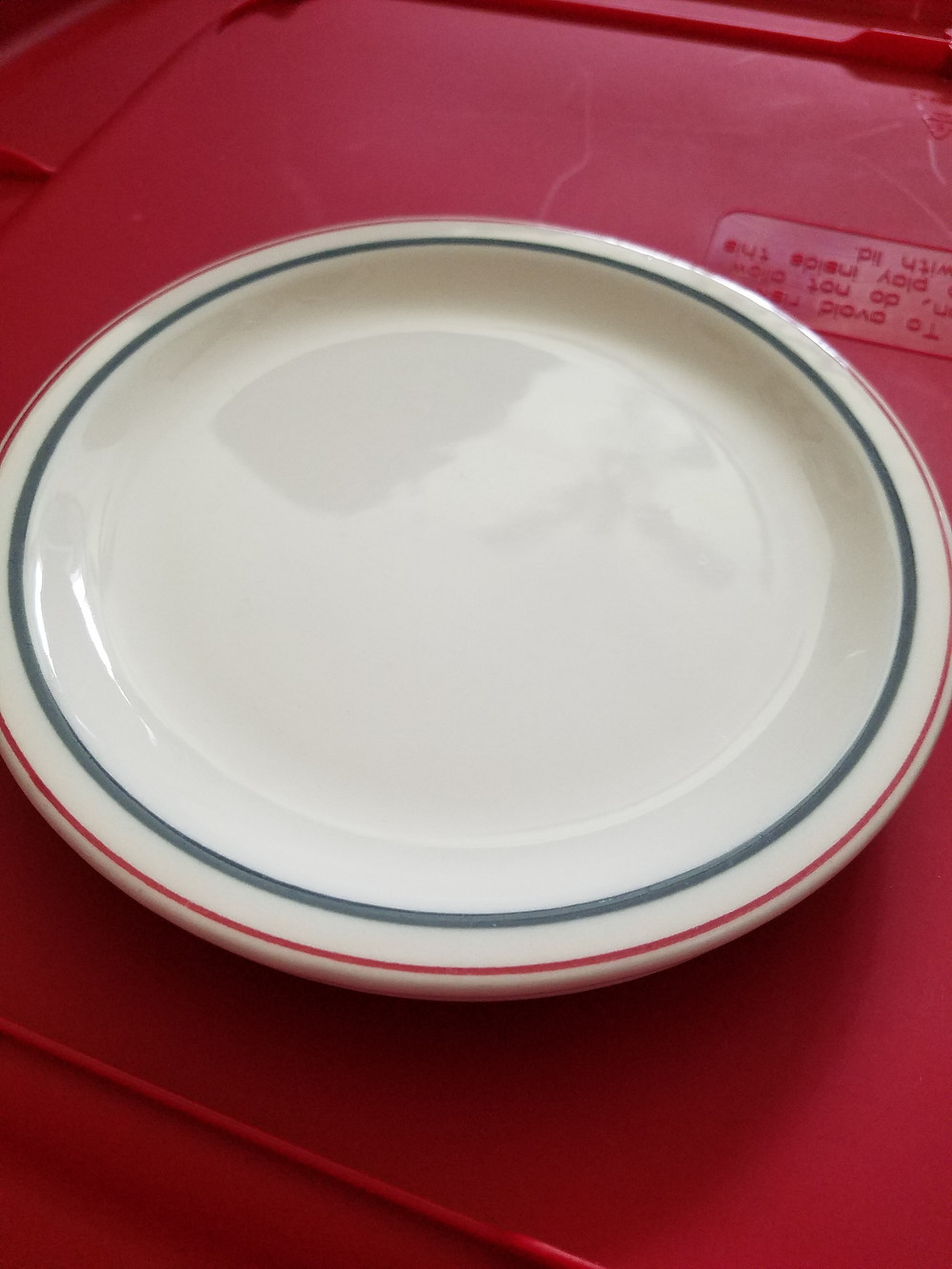 A small desert plate with thin red and blue stripes along the edge.