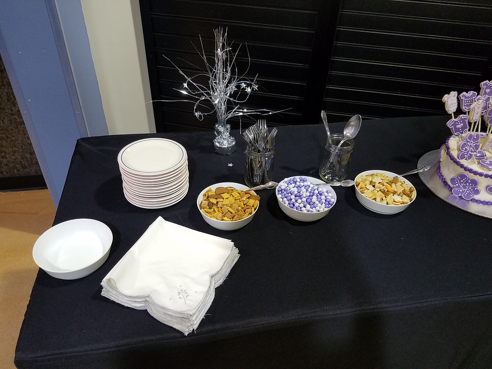 White cloth napkins, a stack of plates, three dishes of snacks in front of two jars of silverware.