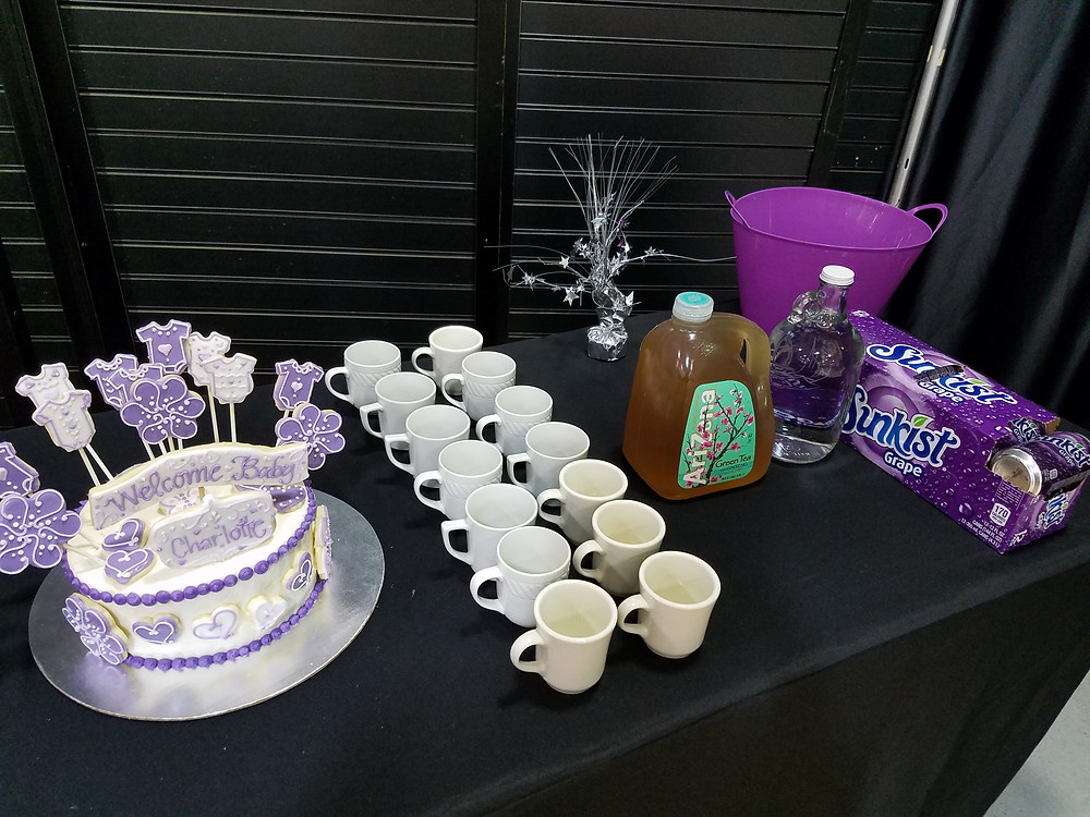 Cake, a set of white mugs, drinks, and the dirty dish bin.