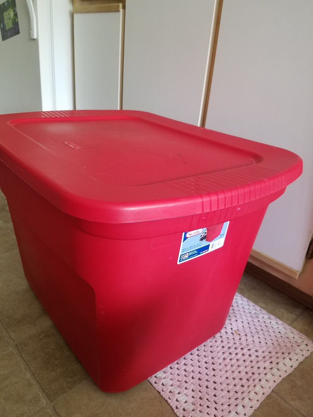 A large, red, 18 gallon storage tub with lid.