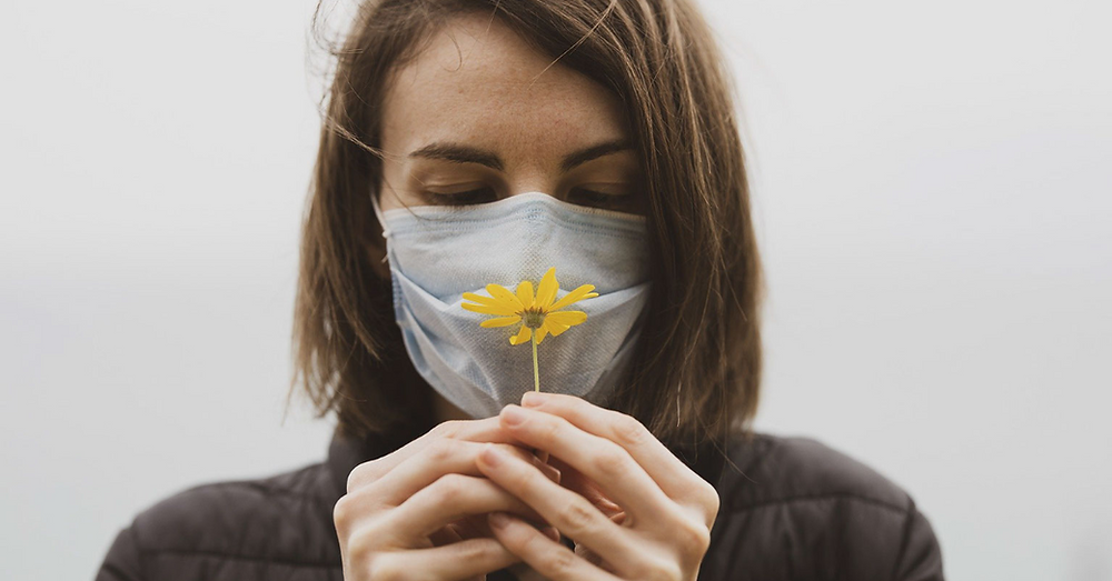 Woman wears face mask during a COVID winter while holding a yellow flower