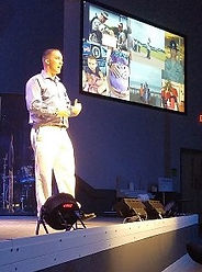 Sean Douglas speaking on stage in Charlotte, NC at icuTalks