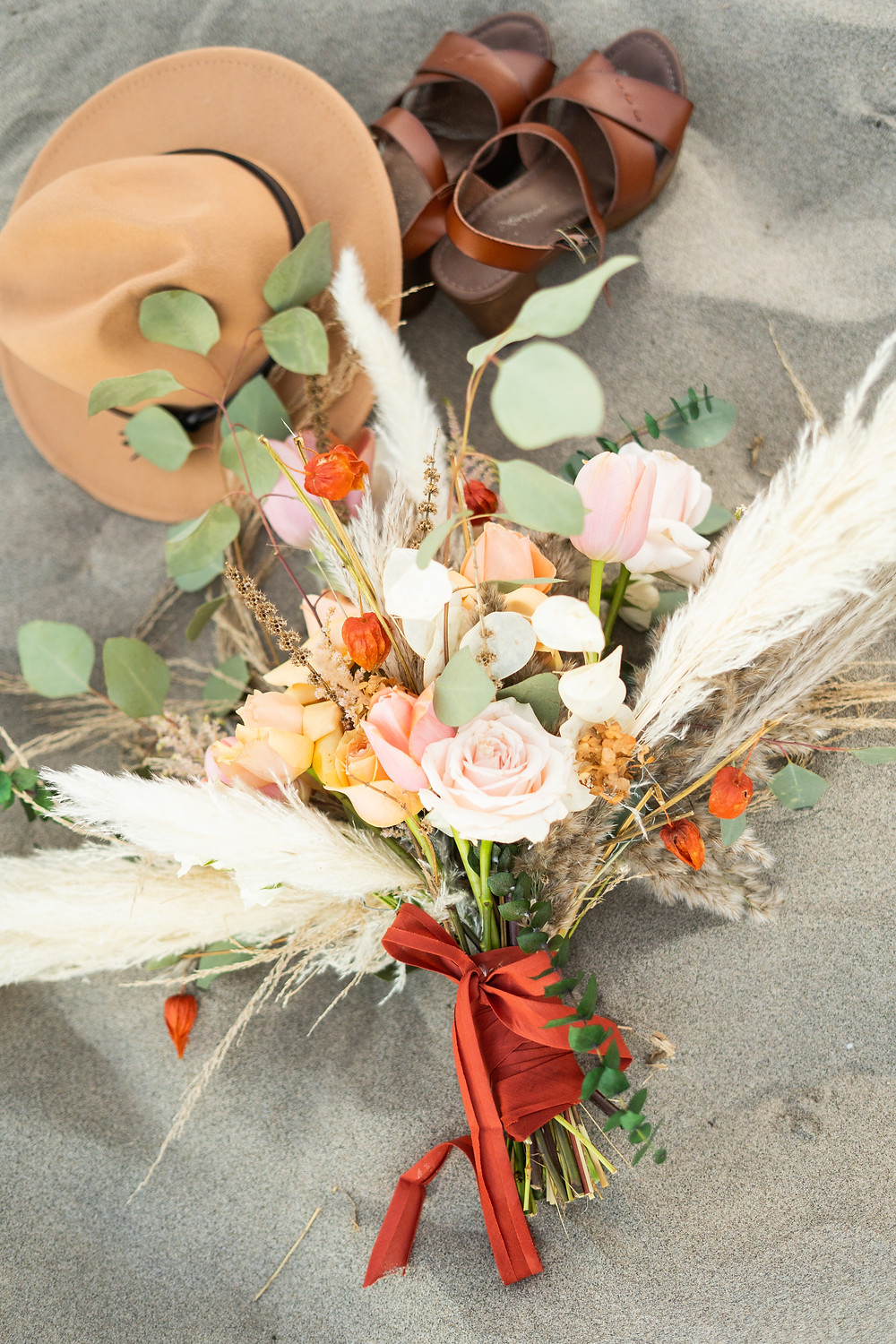 hat, shoes, and pampass grass bouquet in the sand on the beach for an elopement