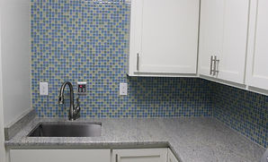granite counter top in mud room with 1x1 glass tile back splash with stainless steel undermount sink and simple white cabinets
