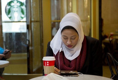 This image is claimed as fair dealing under Australian copyright law. It shows a muslim girl at a starbucks doing everyday things. You don't see that in the media much.