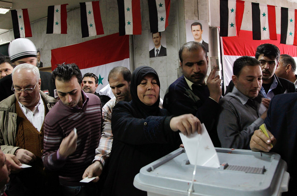 This image is claimed as fair dealing under Australian copyright law. Syrian voters at the ballot box in 2012 casting an overwhelming 'yes' result of 89% in favor of constitutional reform and support for the Assad government.