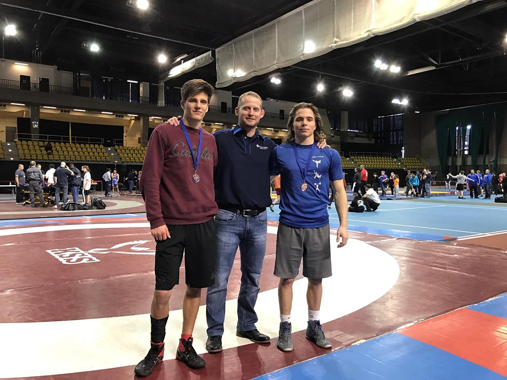 Coach Tom with two male wrestlers at wrestling tournament