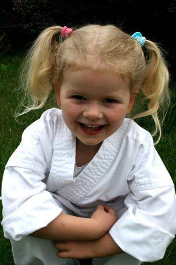 Kinder Karate female young child in gi (karate uniform) smiling