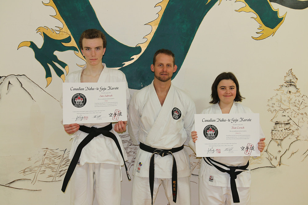 Karate black belt grading students display new certificates of achievement shodan