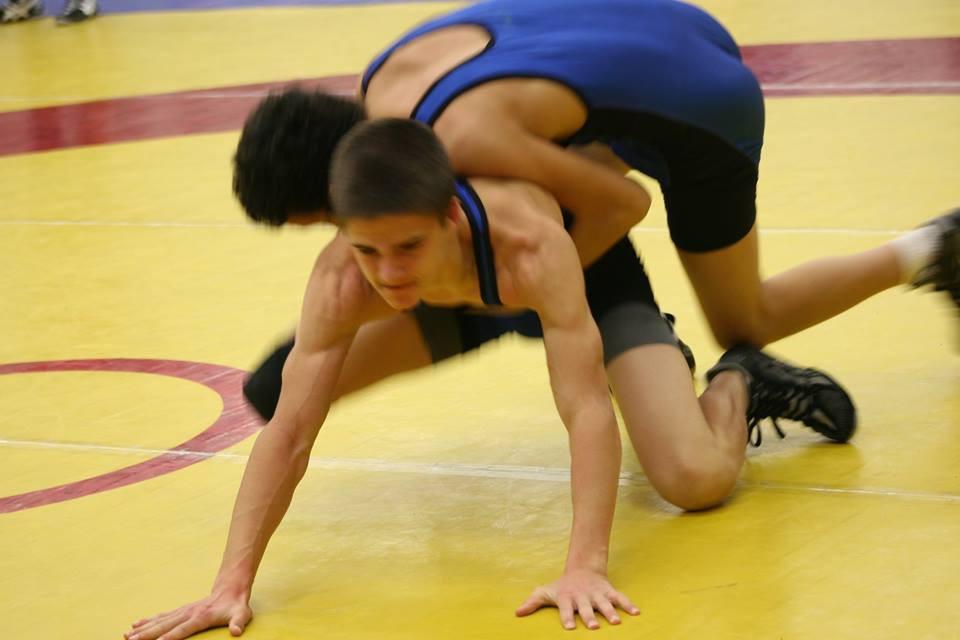 two male wrestlers battle it out on wrestling mats