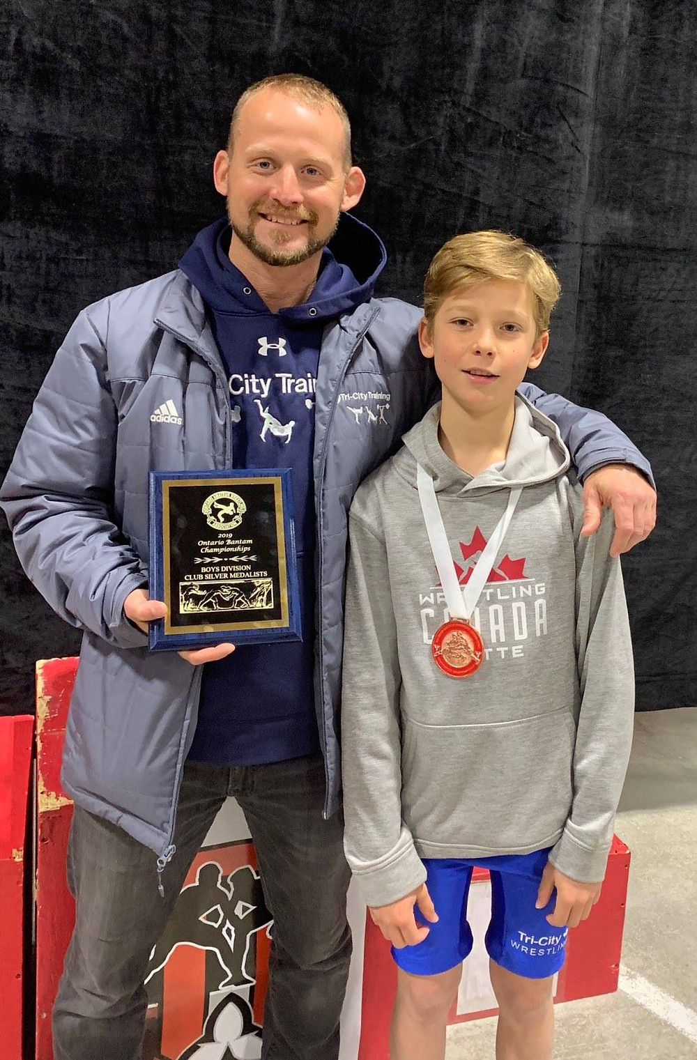 Wrestling coach stands with wrestling athlete both displaying medals won at provincial championships