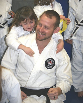 Karate Sensei and Karate Student laughing and smiling during training