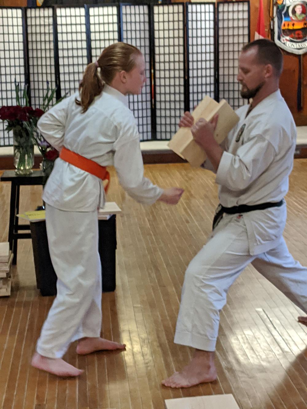 Karate Orange Belt female youth breaks board with Sensei in dojo