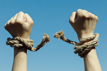 Hands tearing shackles the background of