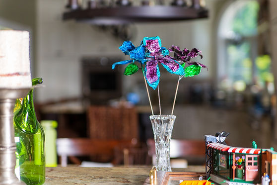 Blue & Purple Roses with Purple Teal Orchid in Crystal Vase by Toys on Kitchen Table