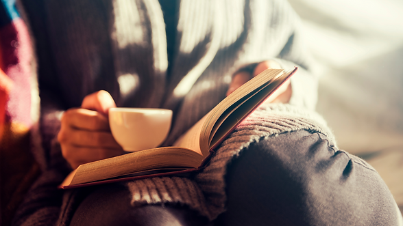 Person reading a book with a cup of tea