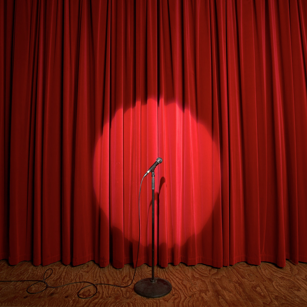microphone on stand with spotlight on it situated in front of red velvet show curtains