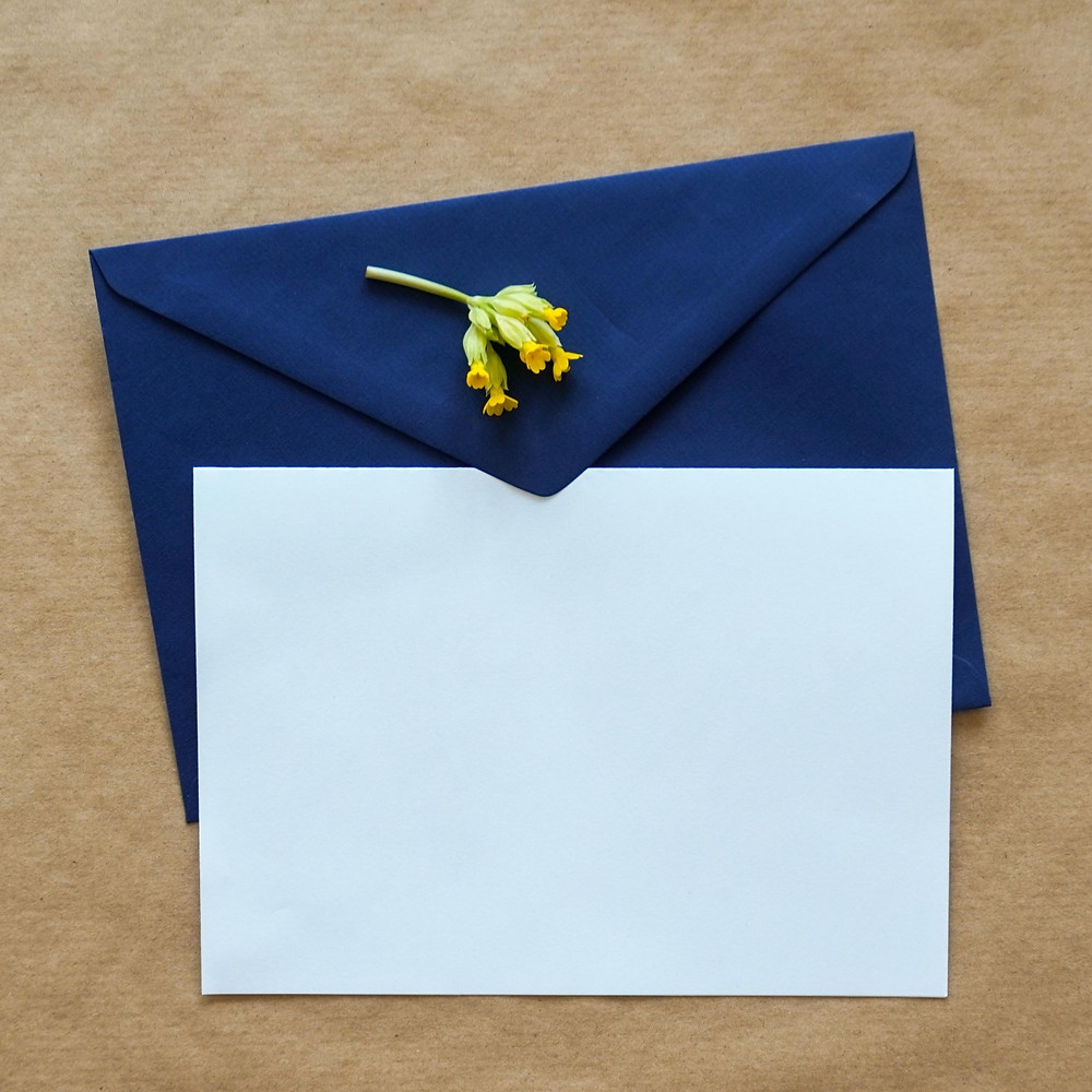 blank letter on blue envelope with a small yellow flower