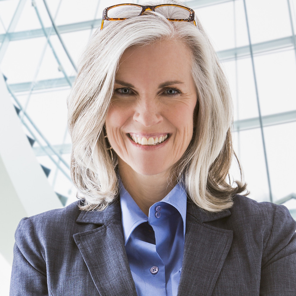 professional woman in a suit with glasses propped on top of her head