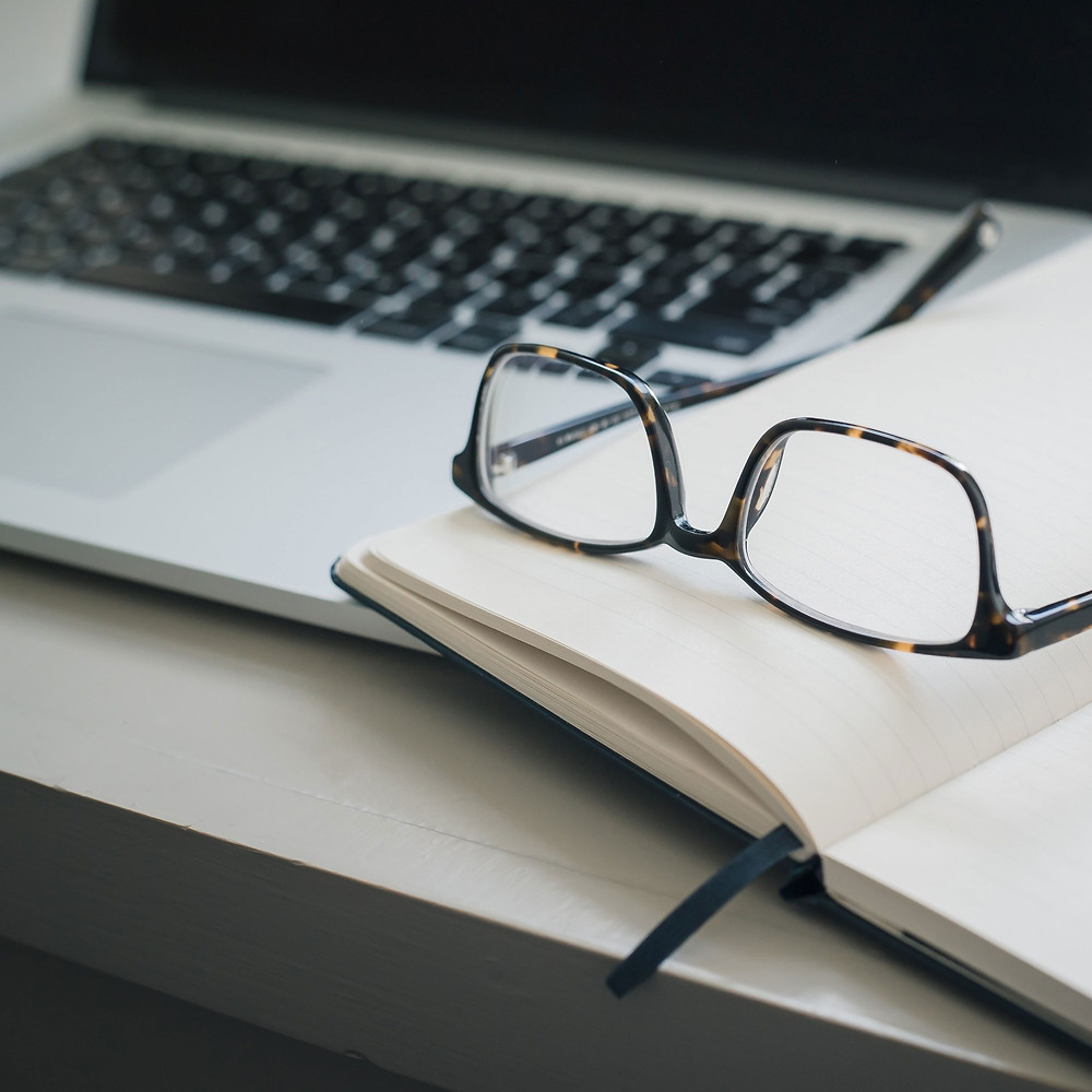 laptop with notebook and reading glasses