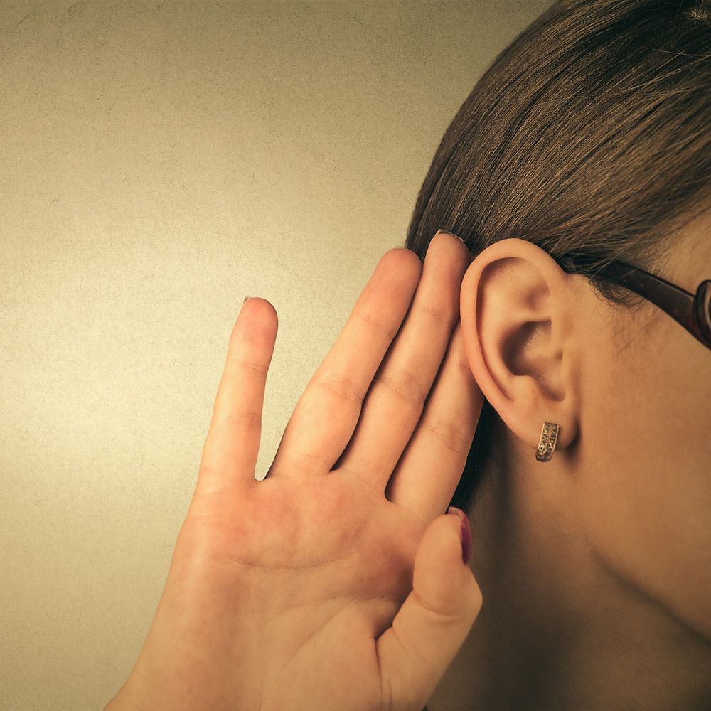 Business woman holding hand to ear as if listening  - on blog post by Mel Butcher