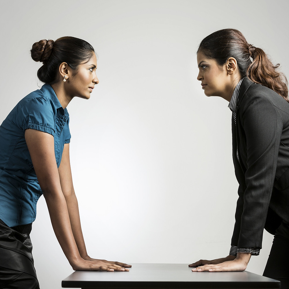 Two business women standing off in competitive pose at a desk