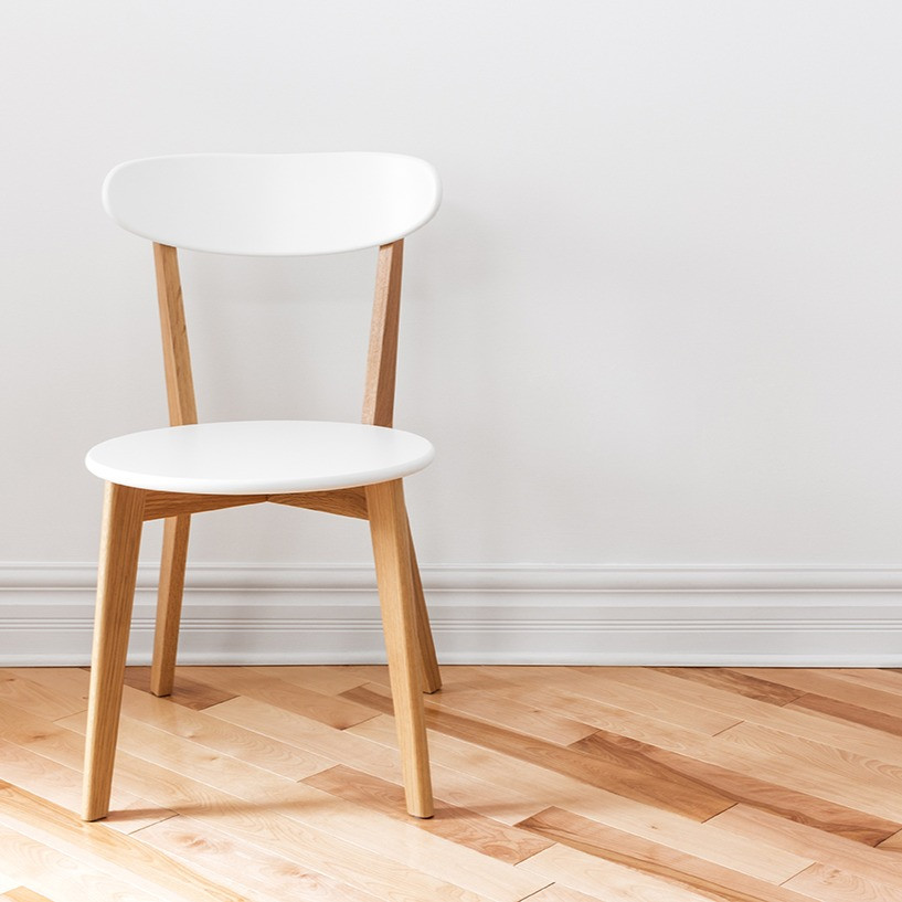 white sitting chair on wood floor in empty room