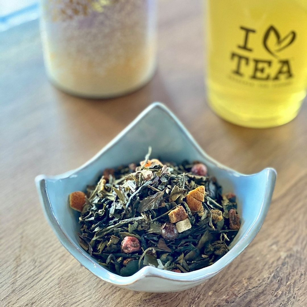 Loose leaf green tea in small bowl with Kaleisia tea glass in background