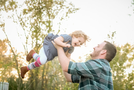 Little girl being thrown in the air by her Daddy