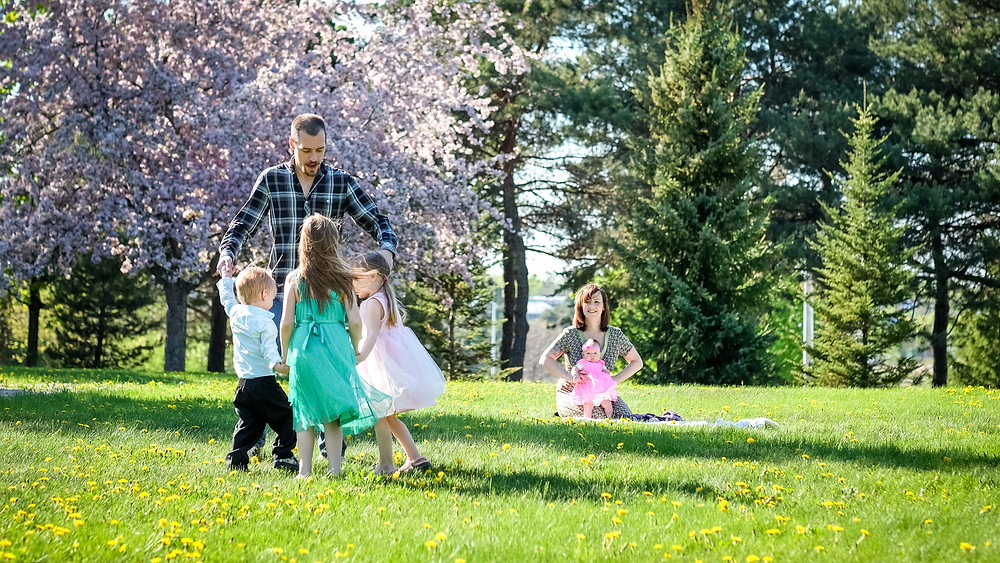 A family dancing together at their family photo session in Belleville, ON