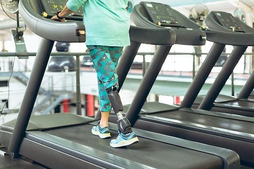 Low section of disabled active senior Caucasian woman with leg amputee exercising on tread