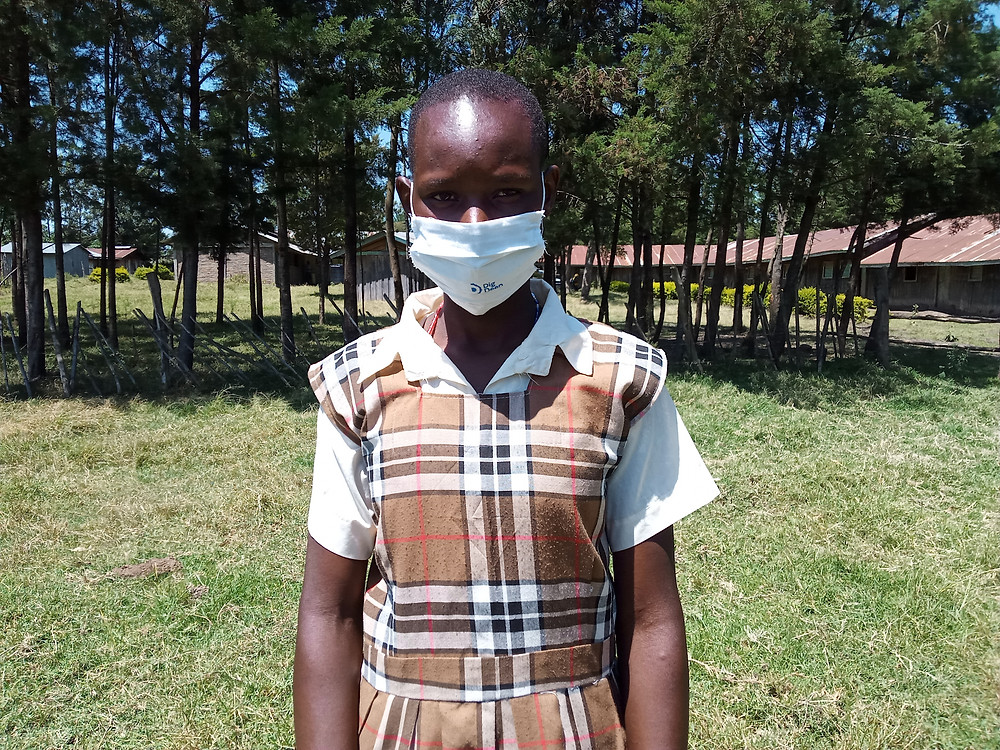Young girl wearing a mask staring at the camera standing in her school grounds