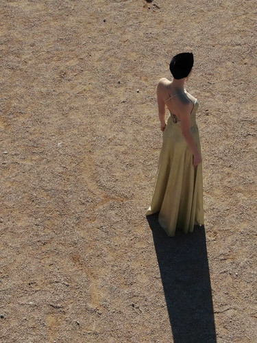a-young-woman-in-an-evening-dress-sits-on-a-sand-a-YM625J3.mov
