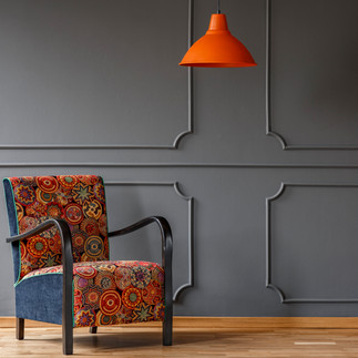 orange-lamp-above-patterned-armchair-in-