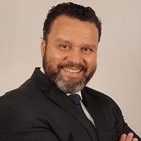 Foto do advogado Dr. José Augusto usando terno preto, com os braços cruzados e um sorriso no rosto.