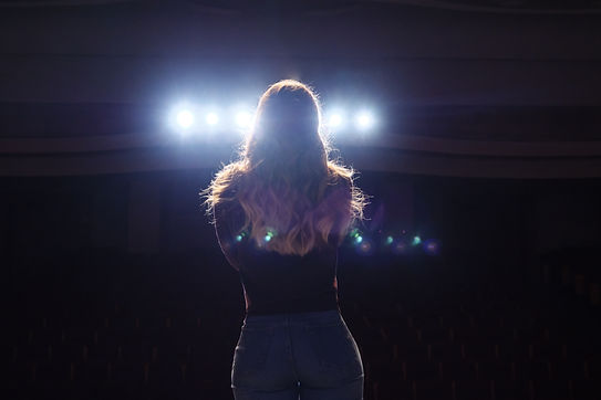 unrecognizable singer standing on stage at microphone in night club, back view.jpg