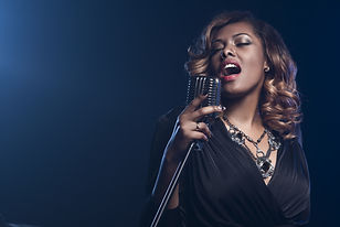 Beautiful African woman singing with the microphone.jpg