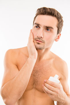 handsome-young-man-holding-lotion-after-