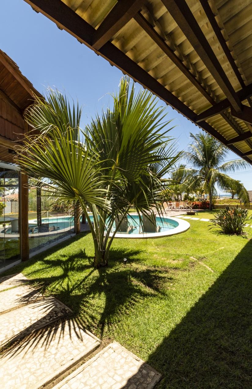 Paisagismos com palmeiras ladeando a piscina