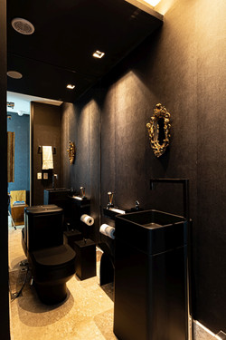 Lavabo preto com papel de parede tipo couro