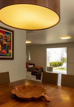 Sala de jantar integrada com lustre de madeira redondo