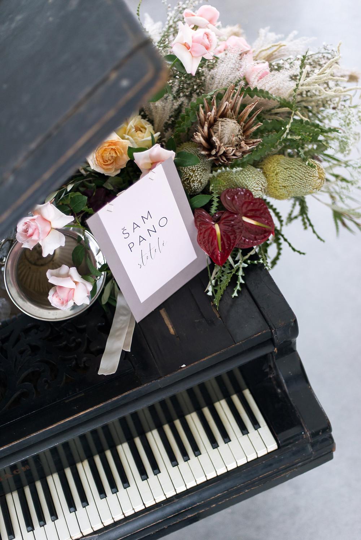 šampano stotelė, pianinas, šventės dekoras su Dekū ir Vynvytis