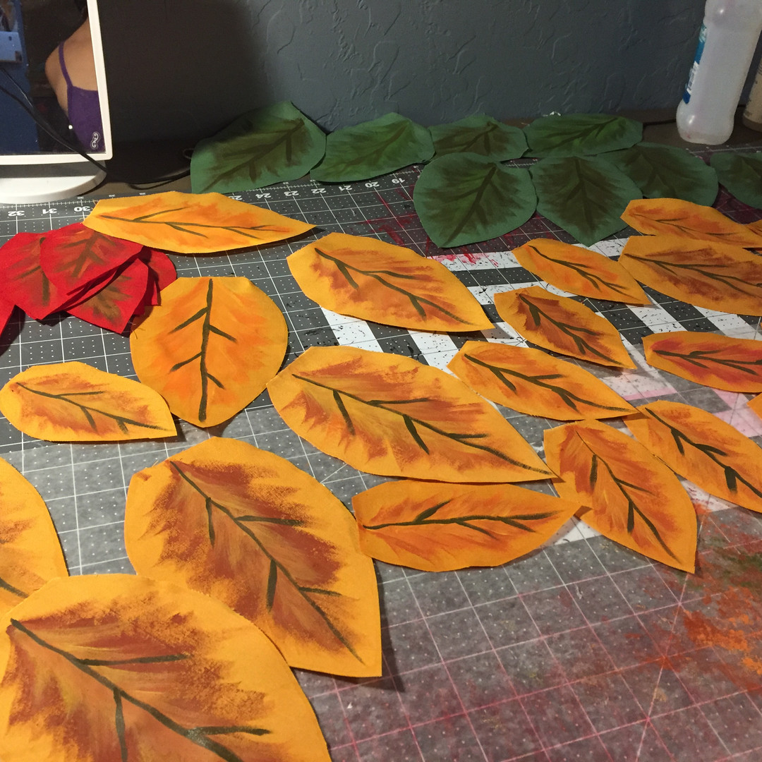 Hand painting fabric leaves.