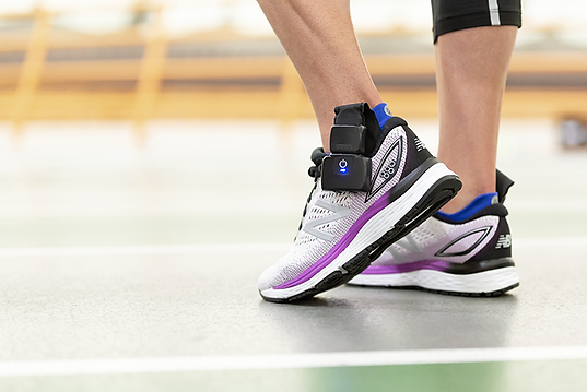 Close-up of an athlete's feet wearing running shoes equipped with XSENSOR's X4 Foot & Gait Measurement system insole sensors.