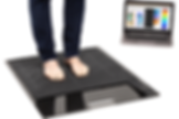 A person standing on XSENSOR's Stance Pad with both feet and a computer in the background running Pro Foot & Gait software displaying the pressure data.