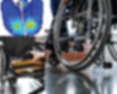 A pressure map, a hand touching a worn out wheelchair seat cushion, and a wheelchair's wheel in focus.